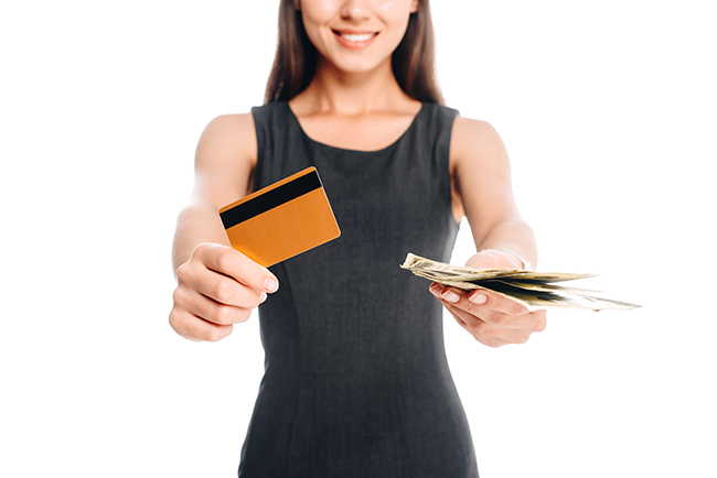 Smiling woman in black dress with credit card and cash isolated on white.